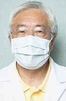 Senior Asian male dentist wearing surgical mask