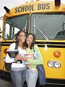 Two young African women with schoolbooks next to school bus