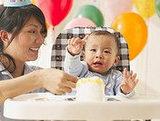 Asian mother and baby in high chair with birthday cake