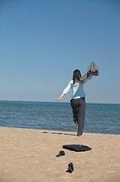 Businesswoman running towards ocean with shoes and briefcase behind her