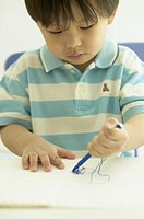 Close up of young Asian boy drawing