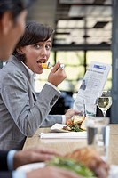 Hispanic businesswoman eating at restaurant