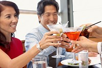 Multi-ethnic friends toasting at restaurant