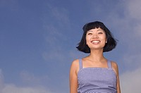 Portrait of Asian woman under blue sky