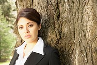 Hispanic businesswoman leaning on tree