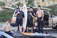 Multi-ethnic surfers being silly next to truck
