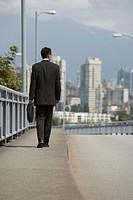 Asian businessman walking on urban bridge