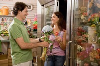 Hispanic couple looking at flowers in florist shop