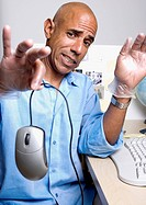 Middle-aged African businessman holding computer mouse