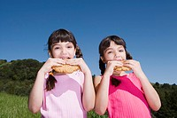 Young Hispanic sisters eating cookies outdoors