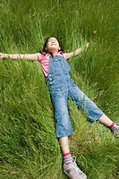 Young girl laying in tall grass