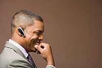 African businessman with earpiece smiling