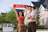 Asian family holding up Sold sign in front of house