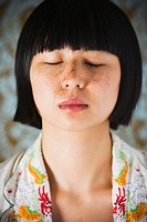 Asian girl with hair clippings on face