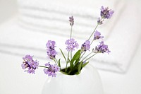 Lavender in vase by towels, close-up