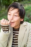 Teenage boy 13-15, finger on nose