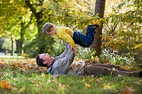 Father lying in meadow, lifting son