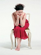 Thinking woman in red sitting on an old whithe chair