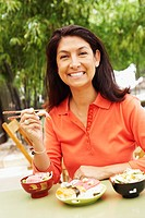Portrait of a mature woman eating with chopsticks