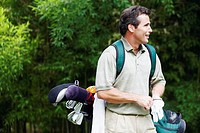 Mature man carrying a golf bag