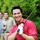 Mature man holding a golf club with his friends standing behind him