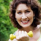 Portrait of a mature woman exercising with a dumbbell and smiling