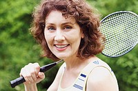 Portrait of a mature woman holding a badminton racket and smiling
