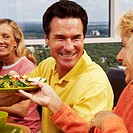 Mid adult woman holding a plate of salad and sitting with a mature couple at the table
