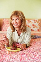 Close-up of a mature woman lying on the bed and eating cake
