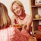 Mature woman giving a bowl of salad to her friend and smiling