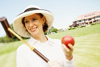 Close-up of a mid adult woman holding a croquet mallet and a ball
