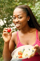 Portrait of a mid adult woman holding a bowl of fruit salad and smiling