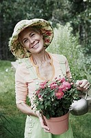 Portrait of a senior woman watering in a potted plant and smiling