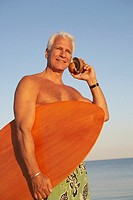 Low angle view of a mature man holding a surfboard and seashell