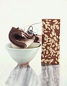 Bar of nut chocolate, bowls with napkin beside it