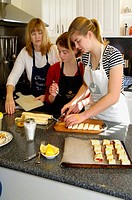 mum teaching cooking to teenage girls