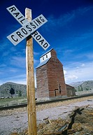 Railroad crossing sign with grain silo in background