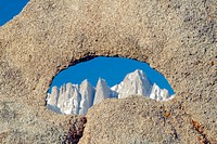The Alabama Hills hole in rock framing snowy mountains at sunrise