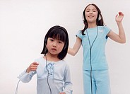 Portrait of two young girls dancing with headphones on