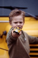 Young boy playing with toy school bus in front of real bus