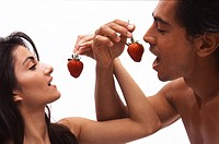 Portrait of a man and woman feeding strawberries to each other