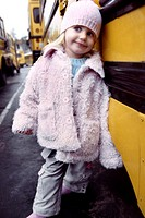 A young girl poses while leaning against a school bus