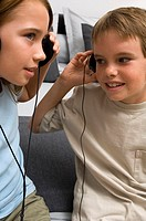 Portrait of two young kids listening to head phones