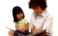 Young boy reading a story to young girl