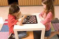 Portrait of Asian boy and Caucasian girl playing checkers