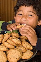Portrait of Hispanic boy eating cookies