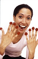 Portrait of a Hispanic female with raspberries on her fingers