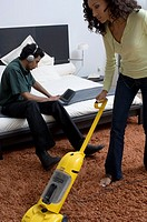Portrait of a man using his laptop while a woman vacuums