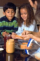 Portrait of boy and girl making sandwiches