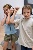 Portrait of two young kids listening to head phones while dancing